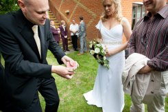 London wedding magician David Fox performing magic to a bride and groom in the grounds of a venue.