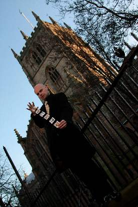 Magician David Fox performing card magic outside a church in London.